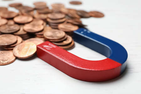 Magnet attracting coins on wooden background, closeup. Business concept