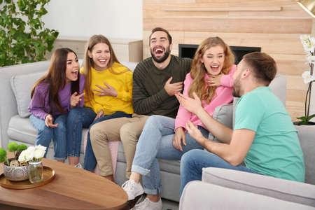 Gruppe von Freunden, die Witze erzählen und im Wohnzimmer lachen