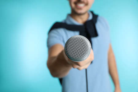 Young handsome man in casual clothes holding microphone on color background, closeup Stock Photo