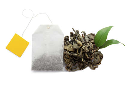 Tea bag and dry leaves on white background, top view