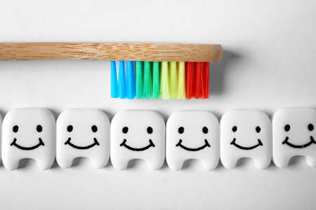 Small plastic teeth with happy faces and wooden brush on white background, top view