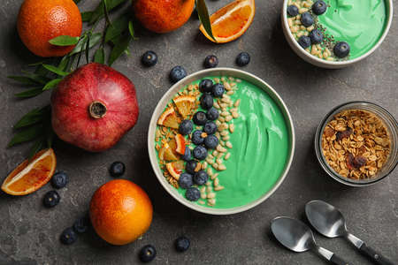 Flat lay composition with bowls of spirulina smoothie on grey background