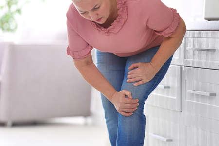 Senior vrouw die lijdt aan kniepijn in de keuken Stockfoto