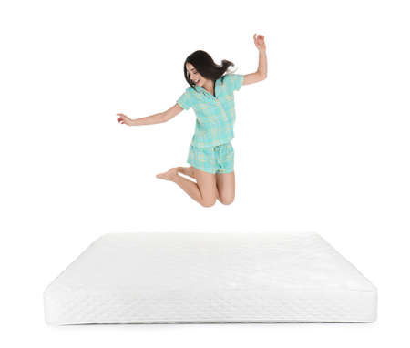 Young woman jumping on mattress against white background Reklamní fotografie