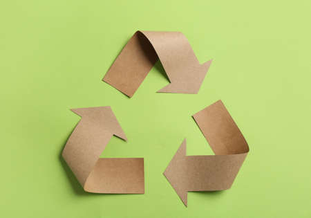 Recycling symbol cut out of kraft paper on green background, top view Foto de archivo