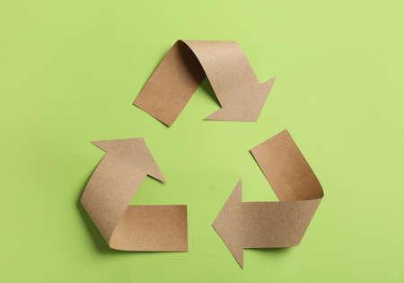 Simbolo di riciclaggio ritagliato dalla carta kraft su sfondo verde, vista dall'alto