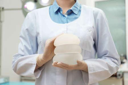 Medico che tiene le protesi al silicone per l'aumento in clinica, primo piano. Chirurgia plastica Archivio Fotografico