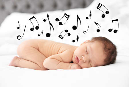 Cute newborn baby sleeping on bed and flying music notes. Lullaby song