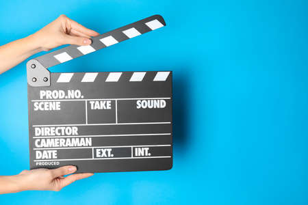 Woman holding clapperboard on color background, closeup with space for text. Cinema production Archivio Fotografico