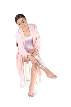 Beautiful young woman shaving leg on white background