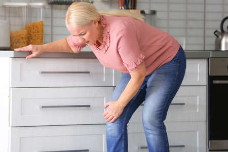Senior woman suffering from knee pain in kitchen Standard-Bild