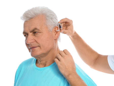Young man putting hearing aid in fathers ear on white background