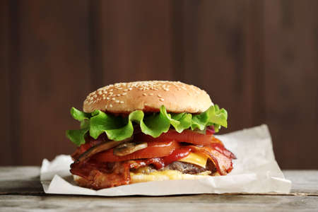 Tasty burger with bacon on wooden table