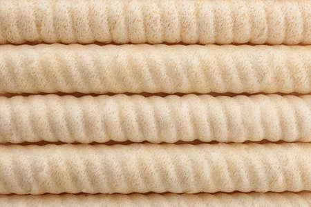 Delicious wafer rolls as background, top view. Sweet food