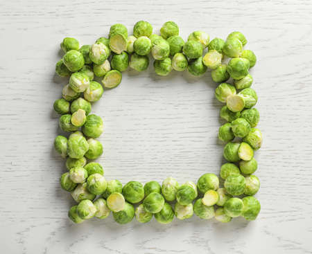 Frame made with Brussels sprouts on wooden background, top view. Space for text