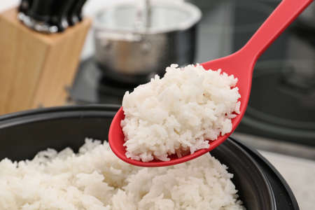 Spoon with boiled rice over cooker against blurred background, closeup 版權商用圖片