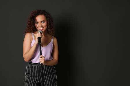 Curly African-American woman in stylish clothes posing with microphone on black background. Space for text