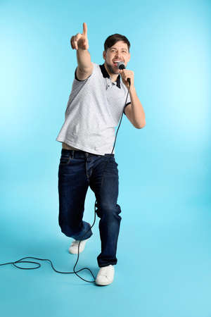 Handsome man in casual clothes singing with microphone on color background