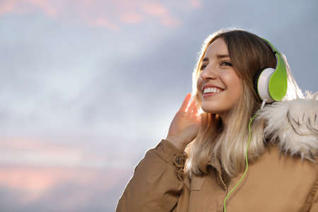Young woman with headphones listening to music outdoors, space for text