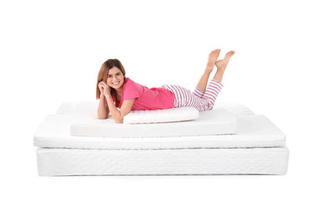 Woman lying on mattress pile against white background