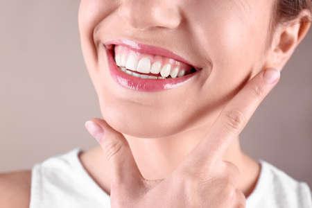 Mujer joven con dientes sanos sonriendo sobre fondo de color, primer plano