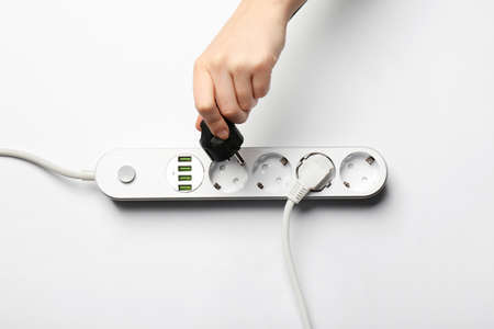 Woman pressing power button of extension cord on white background, top view. Electrician's equipment