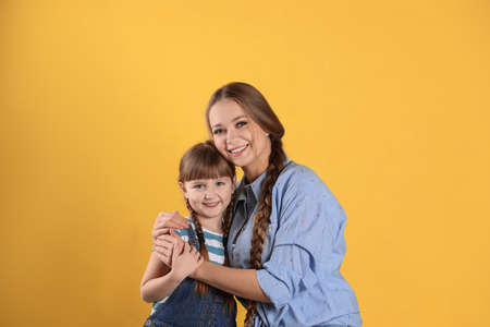 Happy woman and daughter in stylish clothes on color background Imagens