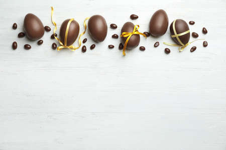 Flat lay composition with chocolate Easter eggs on wooden background, space for text Stock Photo