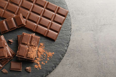 Slate plate with pieces of tasty chocolate on grey background, top view. Space for text