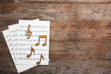 Music notes with sheets on wooden background, flat lay. Space for text