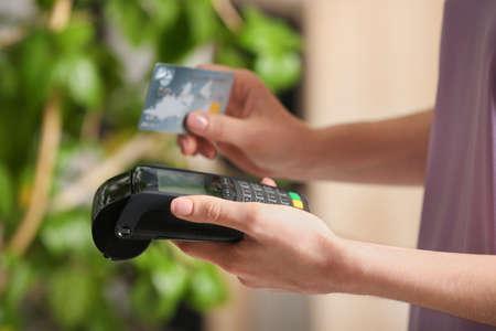Woman using modern payment terminal indoors, closeup