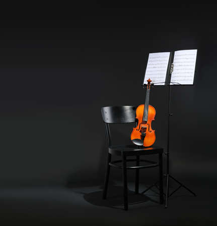 Violin, chair and note stand with music sheets on black background. Space for text