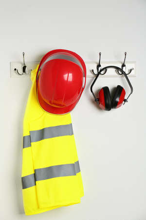 Different safety equipment hanging on white wall Archivio Fotografico