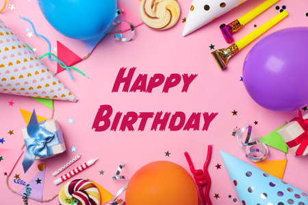Flat lay composition with party items and text Happy Birthday on pink background