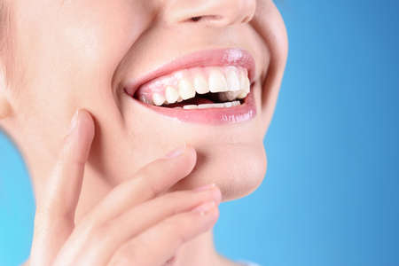 Young woman with healthy teeth and beautiful smile on color background, closeup. Space for text Фото со стока