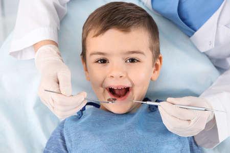Dentista che esamina i denti del ragazzo carino nella clinica moderna Archivio Fotografico