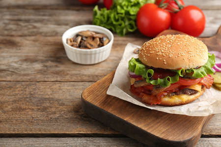 Tasty burger with bacon on wooden board. Space for text Stok Fotoğraf
