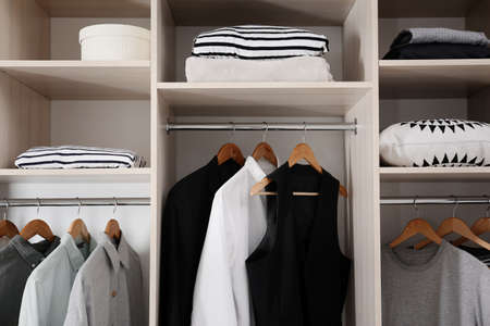 Stylish clothes and home stuff in large wardrobe closet 스톡 콘텐츠