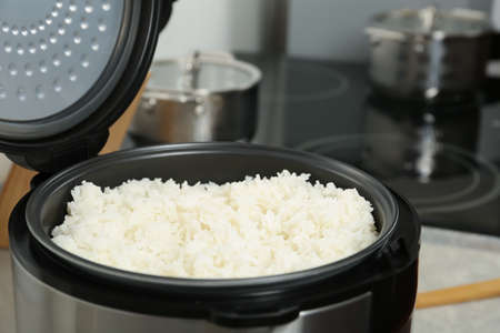 Modern cooker with fresh boiled rice in kitchen