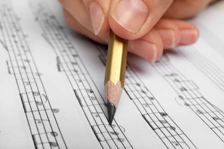 Woman writing music notes on sheet with pencil, closeup