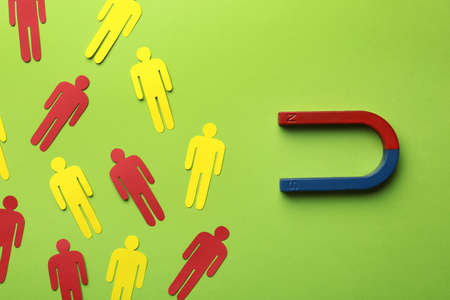 Magnet attracting paper people on color background, flat lay. Marketing concept