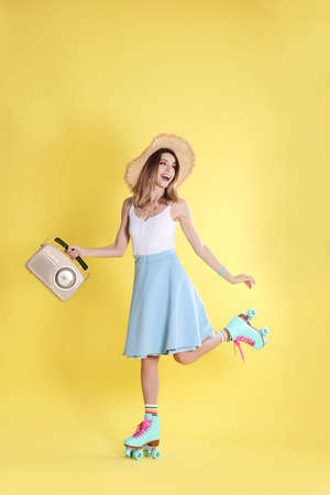 Young woman with roller skates and retro radio on color background Imagens