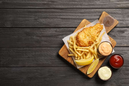British traditional fish and potato chips on wooden background, top view with space for text