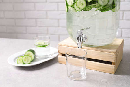 Jar dispenser of fresh cucumber water and glasses on table against brick wall. Space for text
