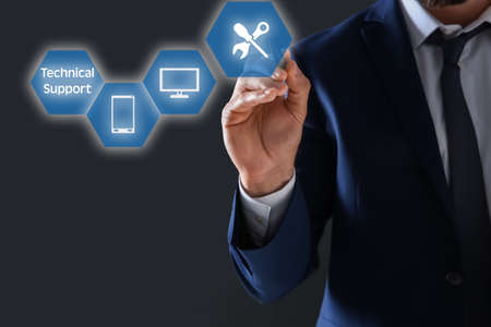 Businessman pressing button on virtual screen against dark background, closeup. Technical support