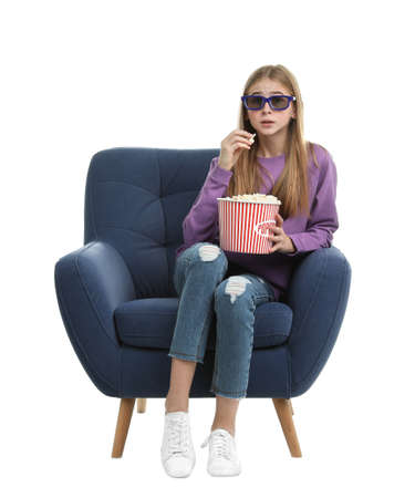 Emotional teenage girl with 3D glasses and popcorn sitting in armchair during cinema show on white background