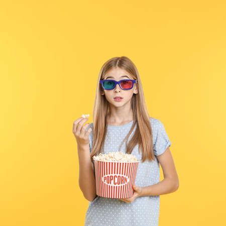 Emotional teenage girl with 3D glasses and popcorn during cinema show on color background