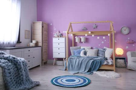 Interno della stanza del bambino con letto comodo e ghirlanda Archivio Fotografico