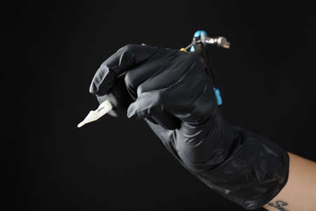 Professional tattoo artist with machine on black background, closeup