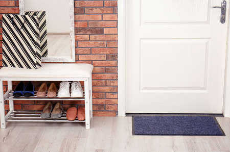Hallway interior with shoe rack, mirror and mat near door